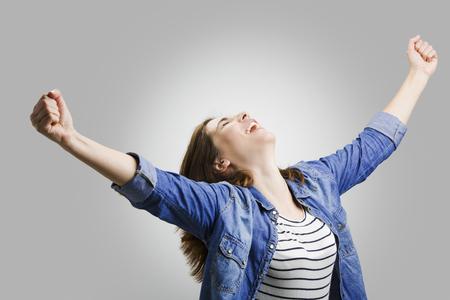 발생한 팔을 가진 행복한 여자의 스튜디오 초상화