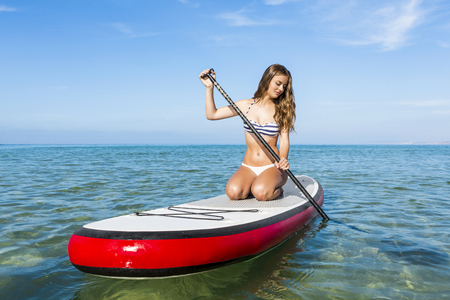 A beautiful woman practicing paddle on a beautiful sunny day Standard-Bild
