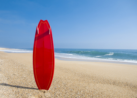 Beach landscape with a red surfboard on the sand 스톡 콘텐츠
