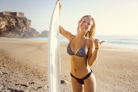 Pretty surfer girl at the beach with her surfbard Archivio Fotografico