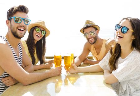 友達と楽しいビーチ バーで冷たいビールを飲んで