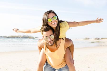 ビーチでの楽しみを持っている若いカップル