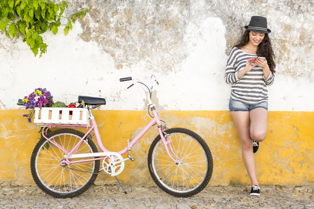 Female tourist living like a local, with her bicycle after buying fresh vegetables Stockfoto