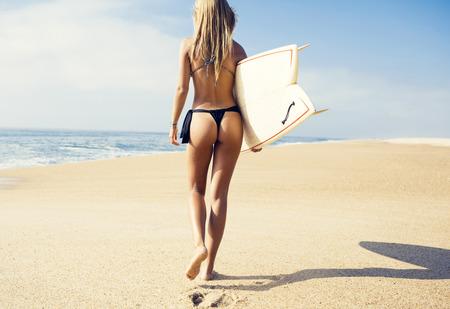 美しく、セクシーなサーファーガール ビーチの上を歩く