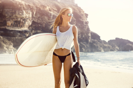 Beautiful young surfer girl walking on the beach Standard-Bild