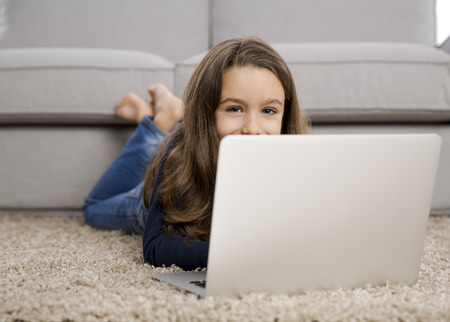 Glückliches kleines Mädchen zu Hause mit einem Laptop