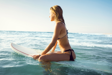 Beautiful young woman sitting on her surfboard waiting for the waves