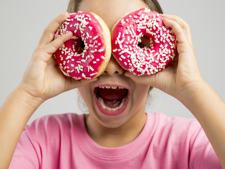 Studio portrait of a beautiful little girl looking through a donut Standard-Bild