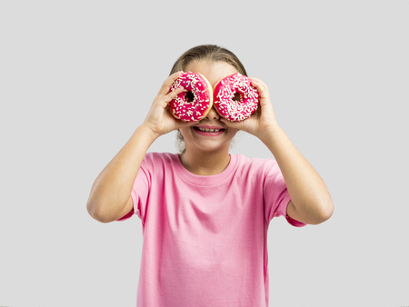 Studio portrait of a beautiful little girl looking through a donut Stock Photo