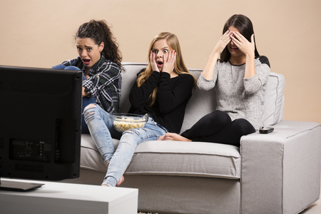 Teenage girls watching horror movie with popcorn Imagens - 56185561