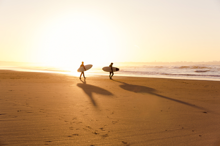 Beautiful beach lansdscape with surfers ready to hit the waves