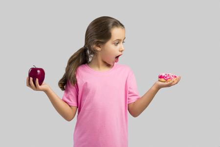 Petite fille souriante et en choisissant entre une pomme et un beignet Banque d'images