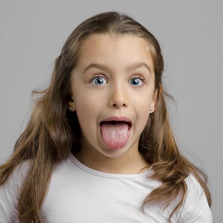 Portrait d'une petite fille avec sa langue