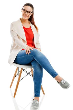 Schöne Frau, die auf einem Stuhl sitzt und lächelnd, isoliert auf weißem Hintergrund