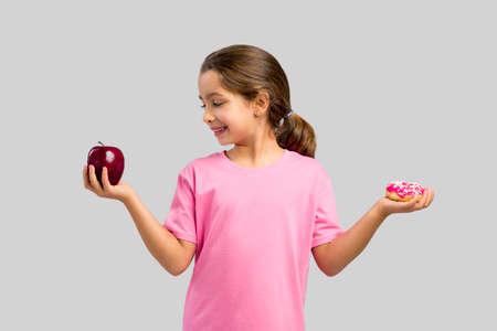 小さな女の子笑顔とリンゴとドーナツの間を選択します。 写真素材