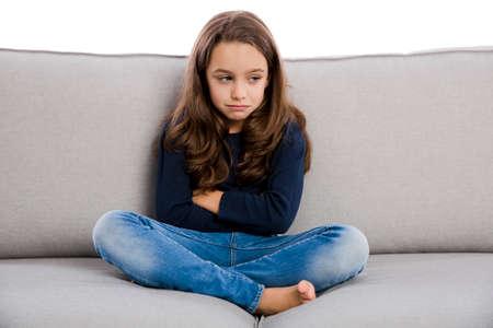 Petite fille assise sur un canapé et bouleversé par quelque chose