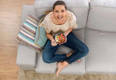 Beautiful happy woman at home eating a healthy bowl
