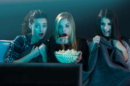 Teenage girls watching horror movie with popcorn Фото со стока - 61282546