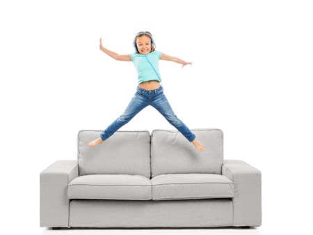 귀여운 금발 소녀 점프 하 고 음악을 듣으십시오.