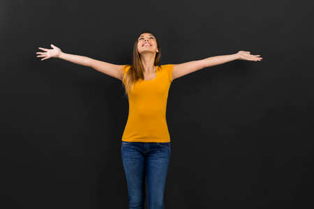 Beautiful woman with arms open in front of a black wall