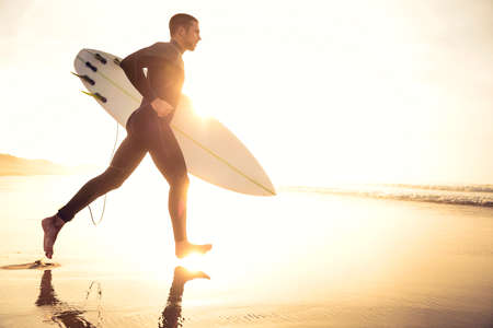 A surfer with his surfboard running to the waves Stock Photo