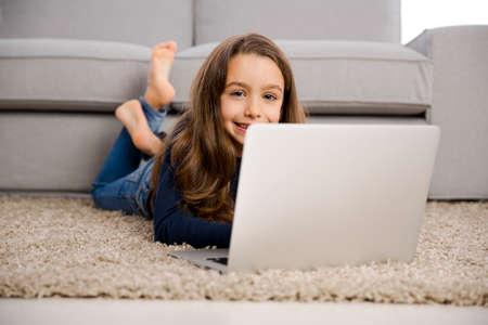 Niña feliz en casa trabajando con un ordenador portátil