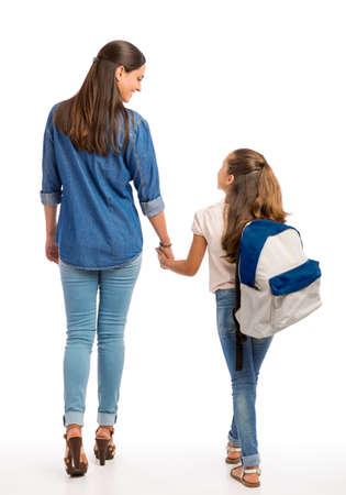 Moeder en haar kleine dochter lopen samen naar de school