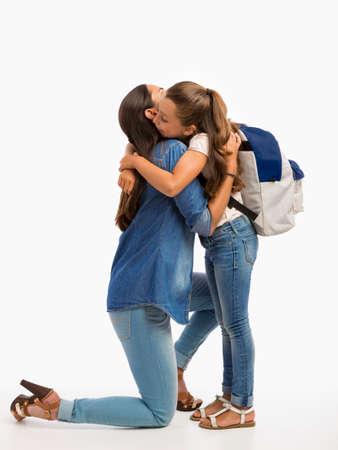 그녀의 작은 딸을 안고 학교 첫날에 작별 인사를하는 어머니 스톡 콘텐츠