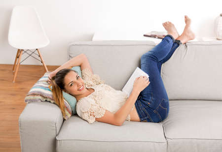 Beautiful woman at home sitting on the couch and reading a book