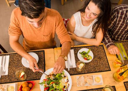 レストランとプレートの食品の提供されている幸せなカップル