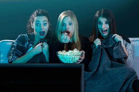 Tieners kijken horrorfilm met popcorn