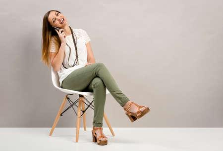 Hermosa mujer joven sentada en una silla y que habla en el teléfono Foto de archivo - 64611527