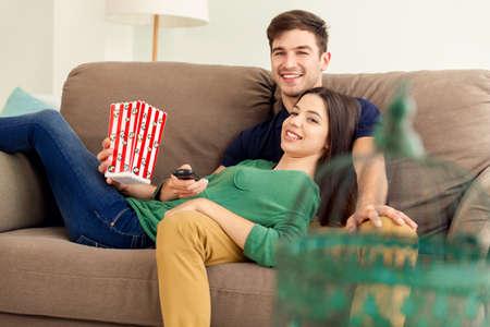 Junges Paar auf dem Sofa und essen popcorns