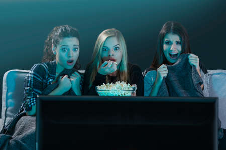 Teenage girls watching horror movie with popcorn Фото со стока - 64612384