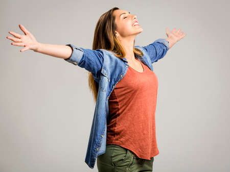 Beautiful happy woman with arms up over a gray background Imagens - 66037717