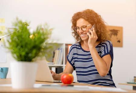 중간 여자 전화를 만드는 사무실에서 세. 스톡 콘텐츠
