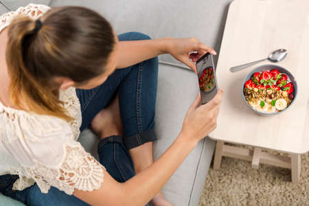 Woman sitting on the couch ready to eat and talking picture to her food Stock Photo