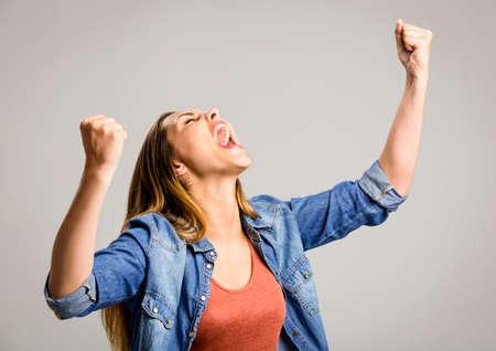 Mooie gelukkige vrouw met de armen omhoog over een grijze achtergrond Stockfoto