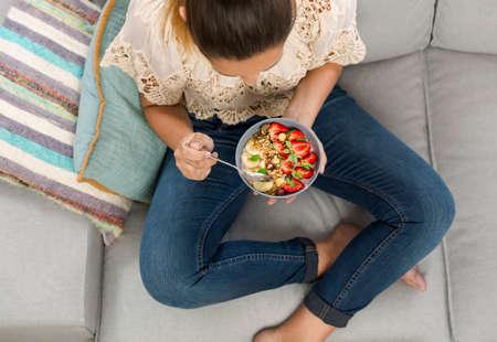 Hermosa mujer feliz en casa comiendo un plato saludable Foto de archivo - 70237232