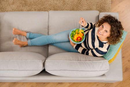 健康的なサラダを食べてソファーで美しい女性のトップ ビュー 写真素材