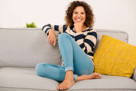 美しい幸せな女を自宅のソファーに座ってください。 写真素材
