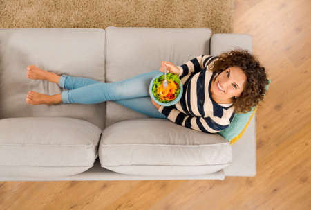 Top view of a beautiful woman on the sofa eating a healthy salade Standard-Bild