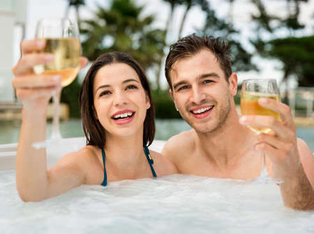 Young couple inside a jacuzzi and toasting
