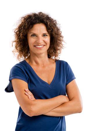 白い背景の上分離した中年の女性を微笑みながら、腕を組んで、