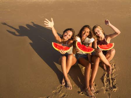 Beste vrienden die plezier hebben op het strand en watermeloen eten Stockfoto