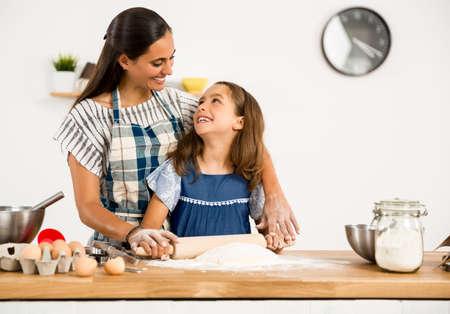母と娘が台所で楽しんで、ケーキを作ることを学ぶのショット