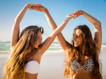 Beautiful girls in the beach giving her hands together Banco de Imagens