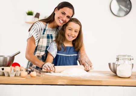 Shot van een moeder en dochter met plezier in de keuken en leren om een ??taart te maken Stockfoto - 75665809