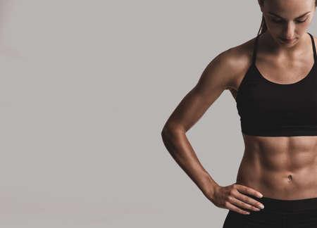 회색 배경에 포즈 근육 질의 몸, 스포티 한 젊은 여자의 초상화 스톡 콘텐츠