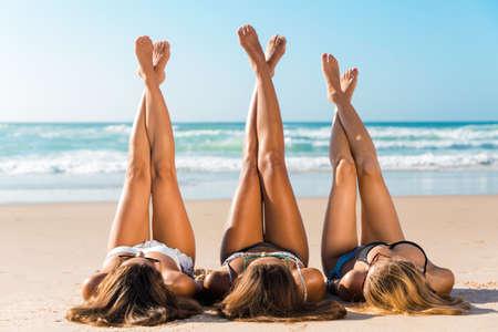 모래에 누워있는 해변에 세 아름다운 여자 스톡 콘텐츠